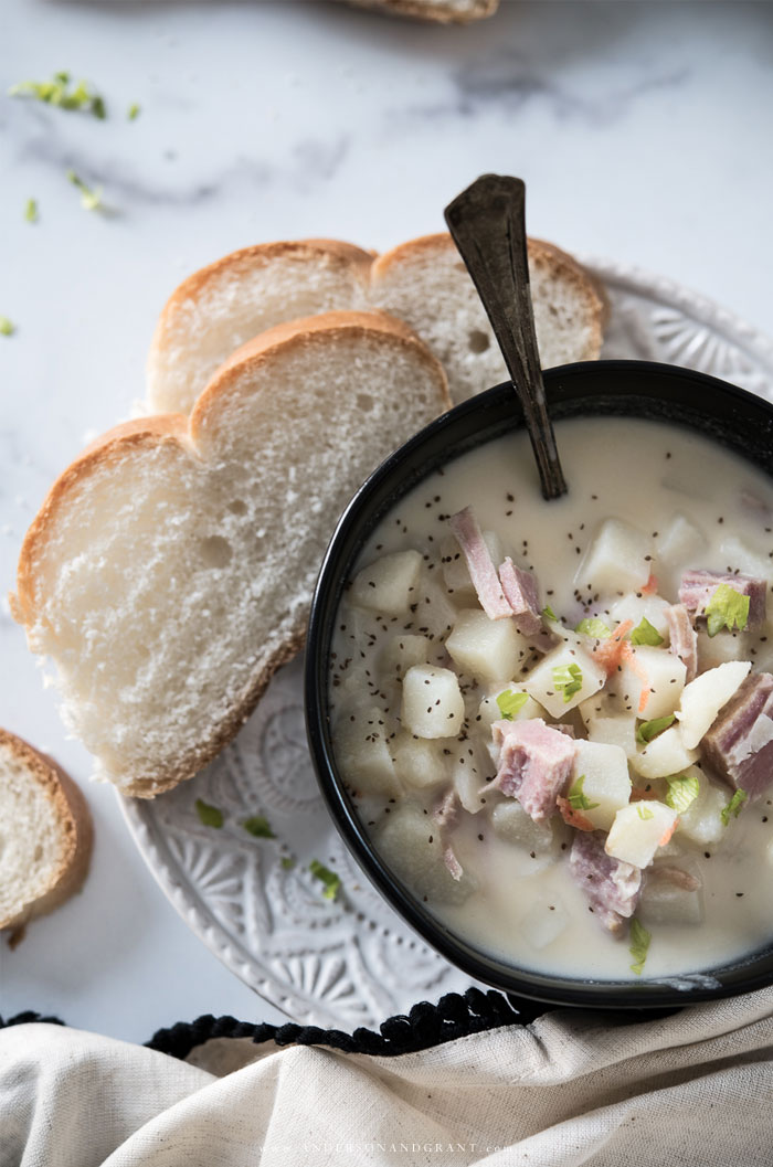 Bowl of potato soup on white plate with bread