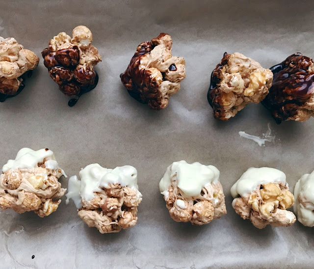 Two rows of popcorn balls, one dipped in white chocolate and another in milk chocolate