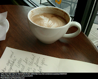 coffee cup on table next to partially complete handwritten letter
