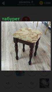 Изящный табурет с красивой обивкой стоит около стола на полу