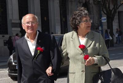 Casal de senhores passeando com cravos vermelhos