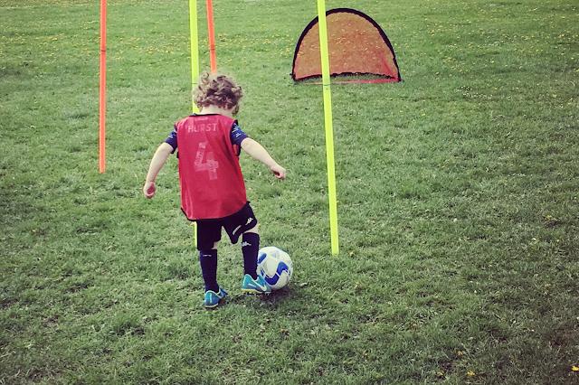 child dribbling football inbetween posts