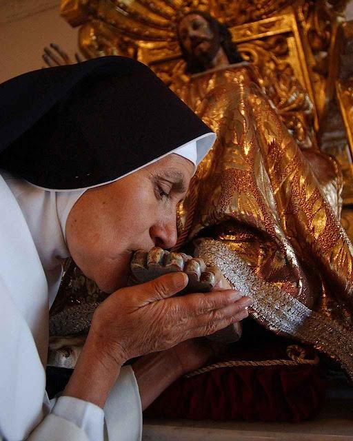 Uma religiosa do mosteiro beija os pés do Cristo das Misericórdias, no claustro do convento. Queira Ele ter pena dos maus sacerdotes e religiosos nesta época tão perturbada.