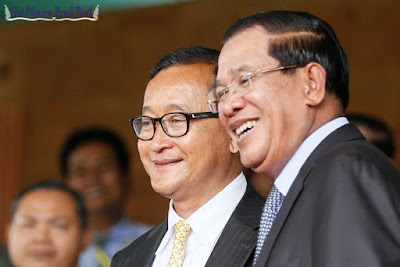 Sam Rainsy, left, and Prime Minister Hun Sen pose for photos after meeting at the National Assembly in 2014. Heng Chivoan