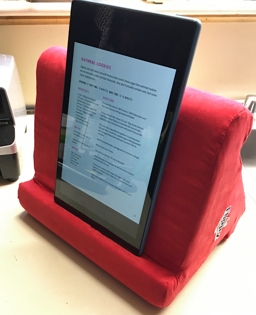 Photo of Flippy pillow stand on a kitchen counter, holding a 10-inch tablet displaying a recipe in a vertical orientation