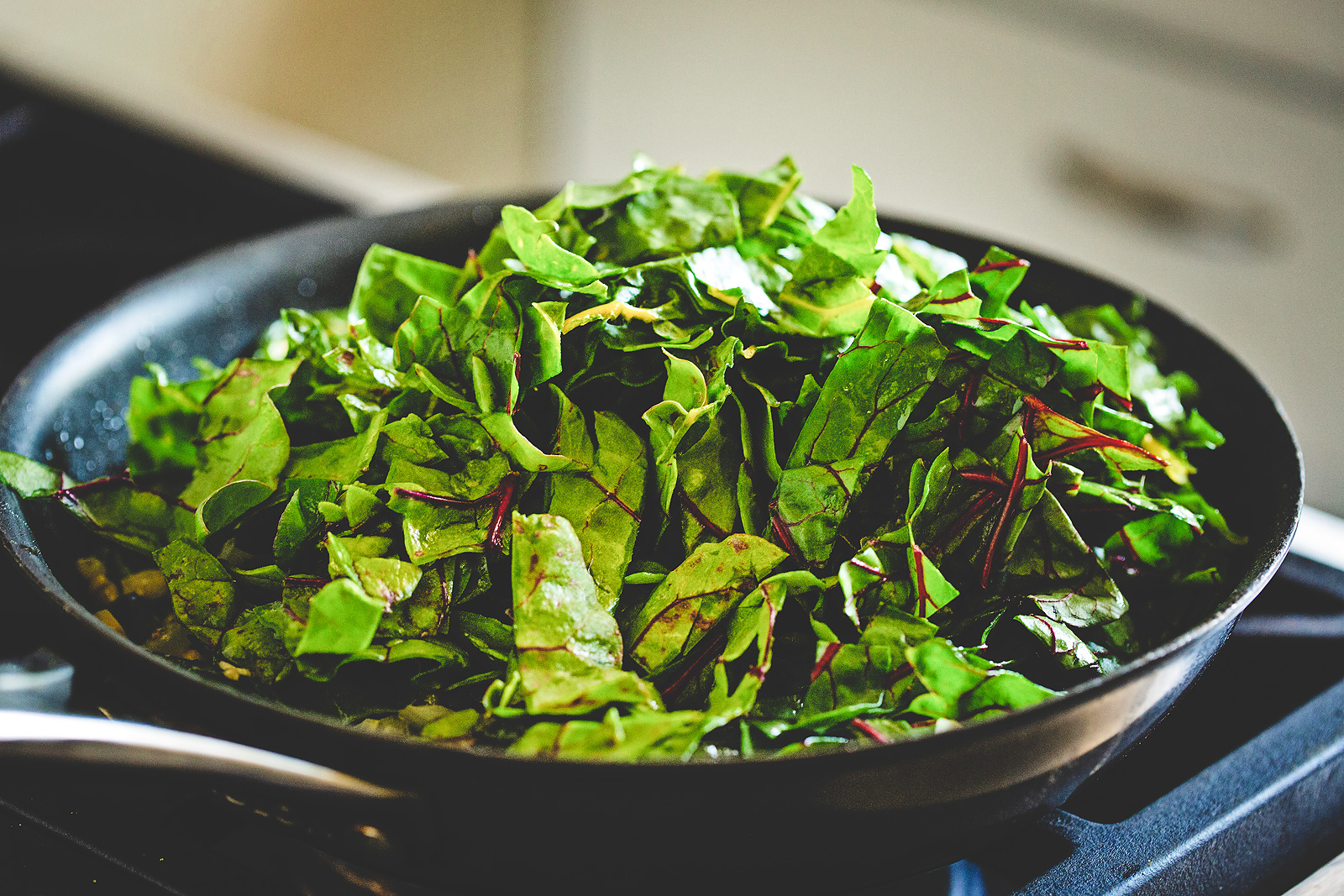 Mound of chard in a skillet on the stove.