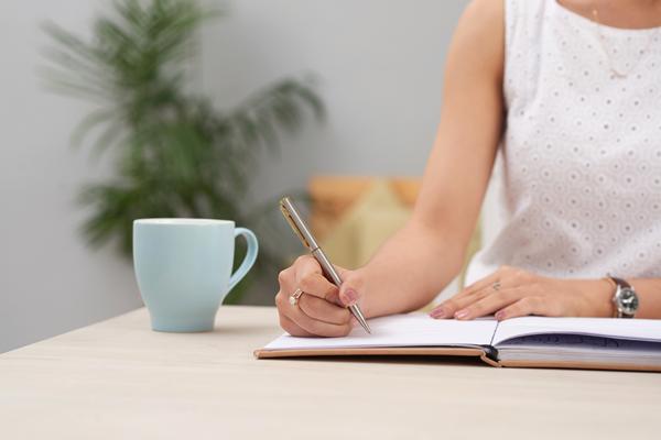 Mulher sentada à mesa escrevendo em um caderno com um caneca azul ao lado