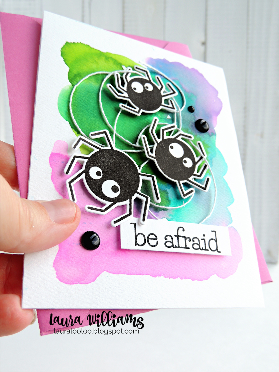 I'm always about COLORFUL handmade Halloween cards, so I wanted to give these stamped and die-cut spiders a fun place to land. I started with a sheet of watercolor paper and added a bit of water plus Jane Davenport Inkredible Inks - they're liquid dye inks that react with water. . .lots of fun to experiment with. I just layered and blended the colors together and let it dry for a bit. Next I gathered up some white twine for the spider web, and popped the spiders on top with foam squares.