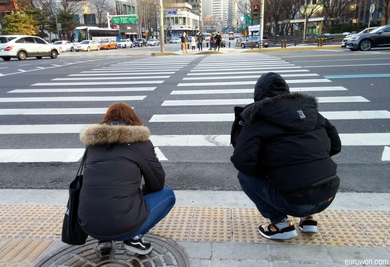 Coreanos en cuclillas en la calle