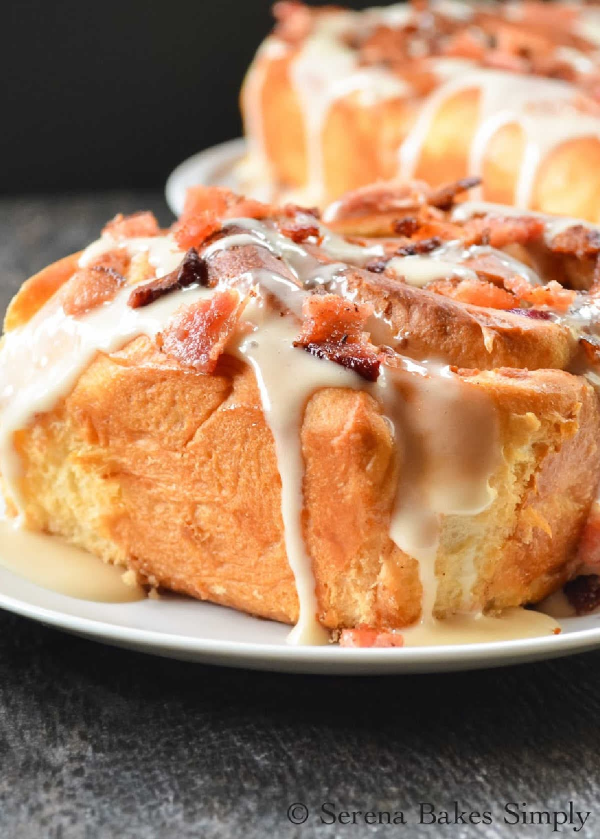 Blueberry Bacon Cinnamon Rolls topped with bacon crumbles on a white plate.
