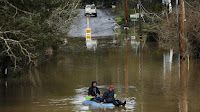 Flood Watch: Residents paddle along River Lands Road in Guerneville. (Credit: John G. Mabanglo / European Pressphoto Agency) Click to Enlarge.