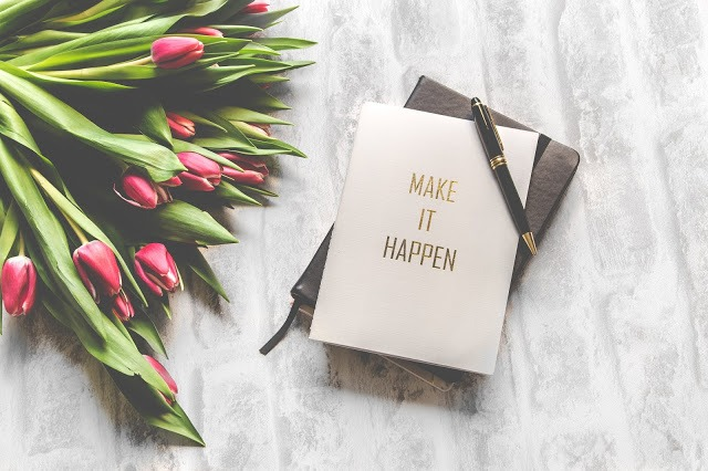 Notebook that says make it happen. The image also has some red tulips
