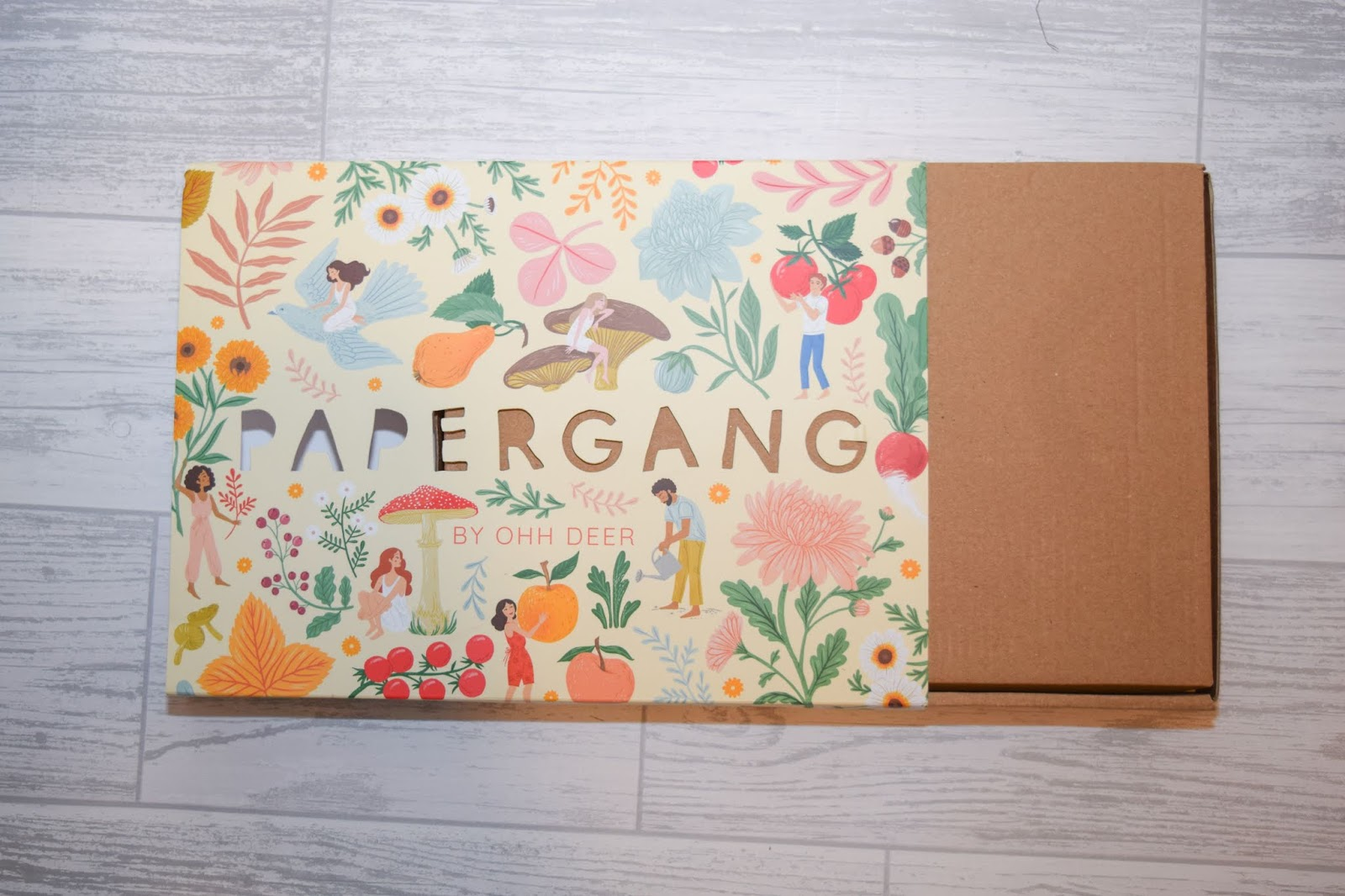 A box sleeve half pulled away with a vegetable and wildflower print on the front.