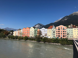 A view of colored row houses, a river, and mountains in the background.