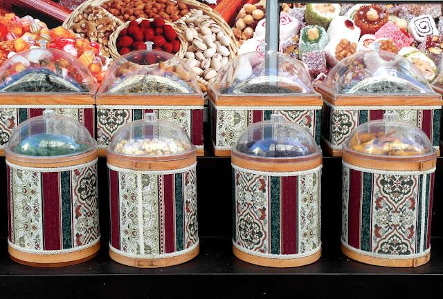 Nüsse, geröstete Kerne und so in bunten mit arabischer Kalligrafie verzierten Behältern