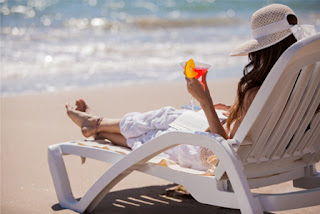 Looking from behind at a woman with dark hair wearing a white hat and clothes sitting in a white chair while reading a book on a beach.