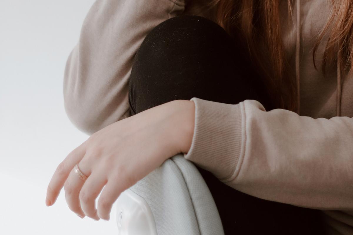 Jeune femme assise et pensive veut se détacher du besoin de reconnaissance