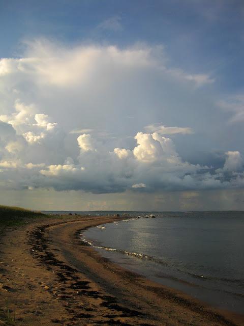 Harjusaaren kapea hiekkainen niemi, jota ympäröi meri. Taivaalla on sadepilviä.