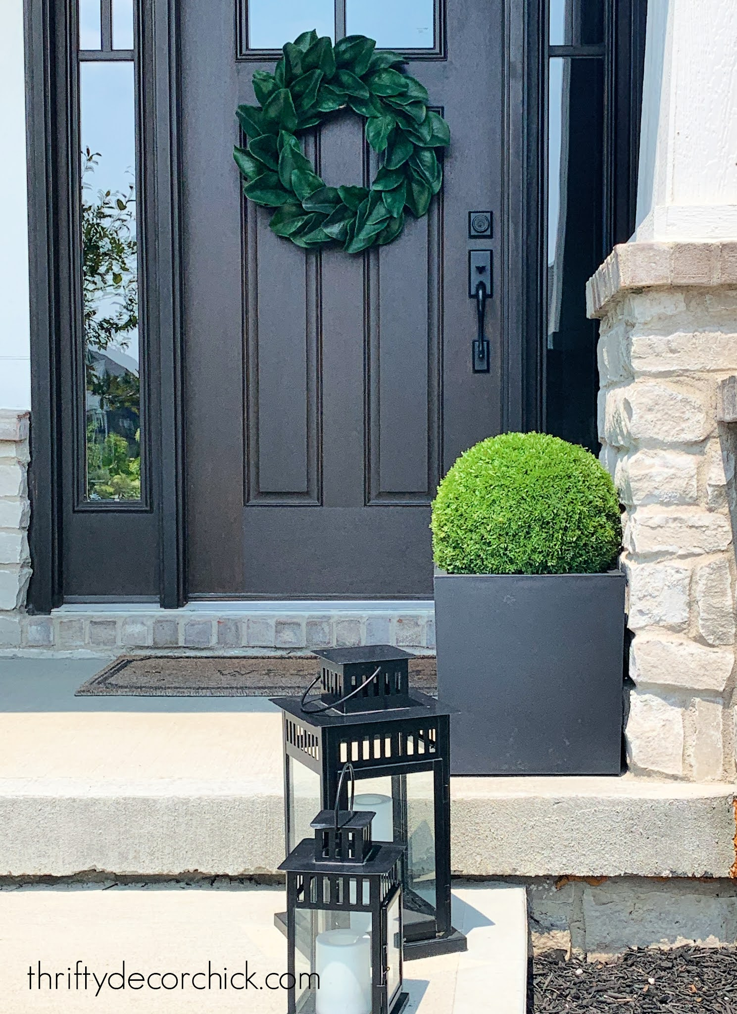 black planter with green boxwood on porch