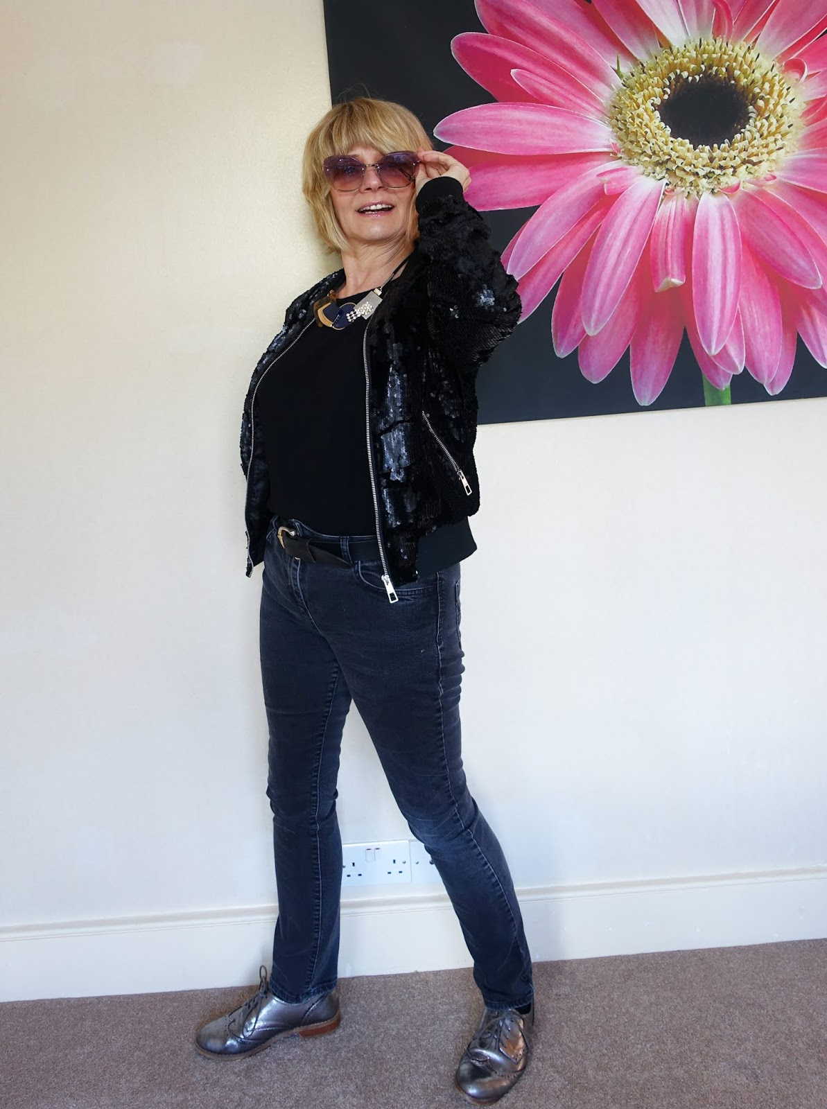 Off to a rock concert wearing all black with a matte sequin bomber jacket black jeans and sunglasses