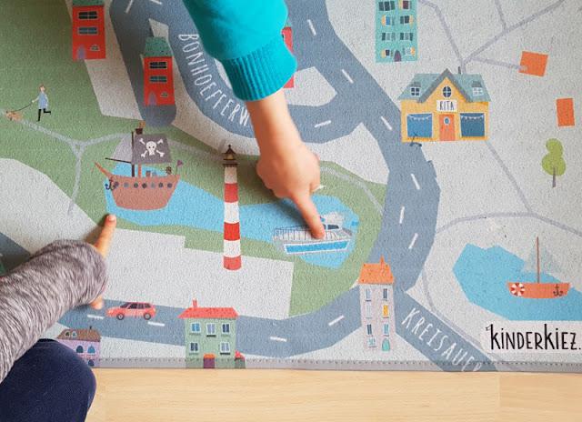 Spielend im eigenen Kiez unterwegs: Unsere Erfahrungen mit dem Spielteppich von kinderkiez. Die eigene Nachbarschaft, der eigene Stadtteil und das eigene Haus auf dem Teppich im Kinderzimmer: Ich zeige Euch auf Küstenkidsunterwegs einen personalisierbaren Kinderteppich, den Ihr online individuell gestalten und den die Kinder analog toll bespielen können.