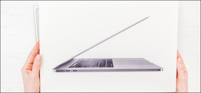 يد تحمل صندوق Apple MacBook Pro.