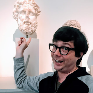 Greig Roselli stands next to a bust of Zeus at the Metropolitan Museum of Art Greek and Roman wing.