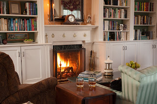 Chair and sofa with sidetable set with whiskey glasses before a fireplace surrounded by white bookshelves
