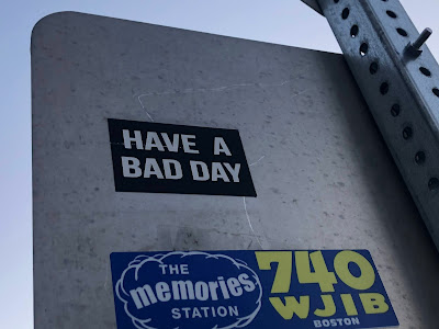 """Sticker on back of street sign saying, """"Have a Bad Day"""""""