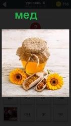 Запечатанная банка с медом и желтые подсолнухи с которых пчелы собирали нектар для него