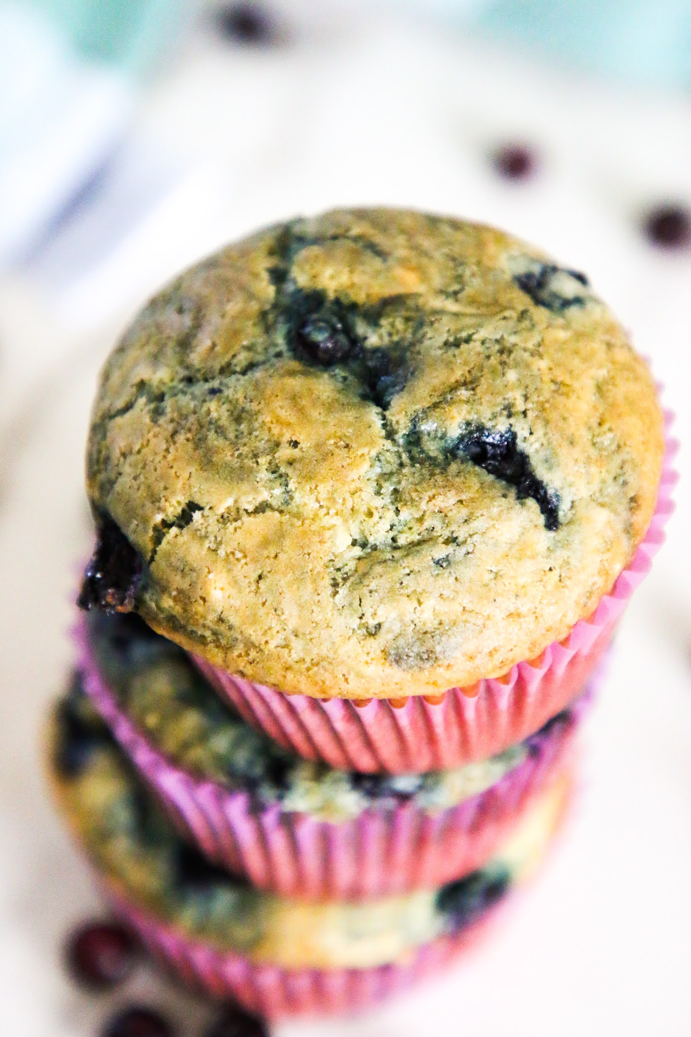 Three blueberry muffins stacked on top of each other on a marble table with blueberries scattered in the background.