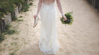 Novia con escote en la espalda caminando por la playa