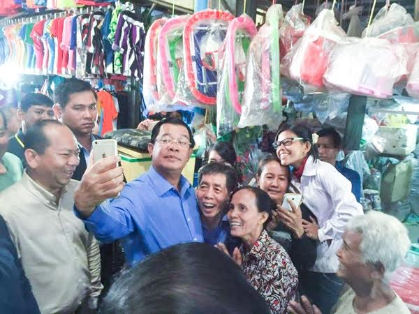 Prime Minister Hun Sen takes a selfie with supporters. Supplied