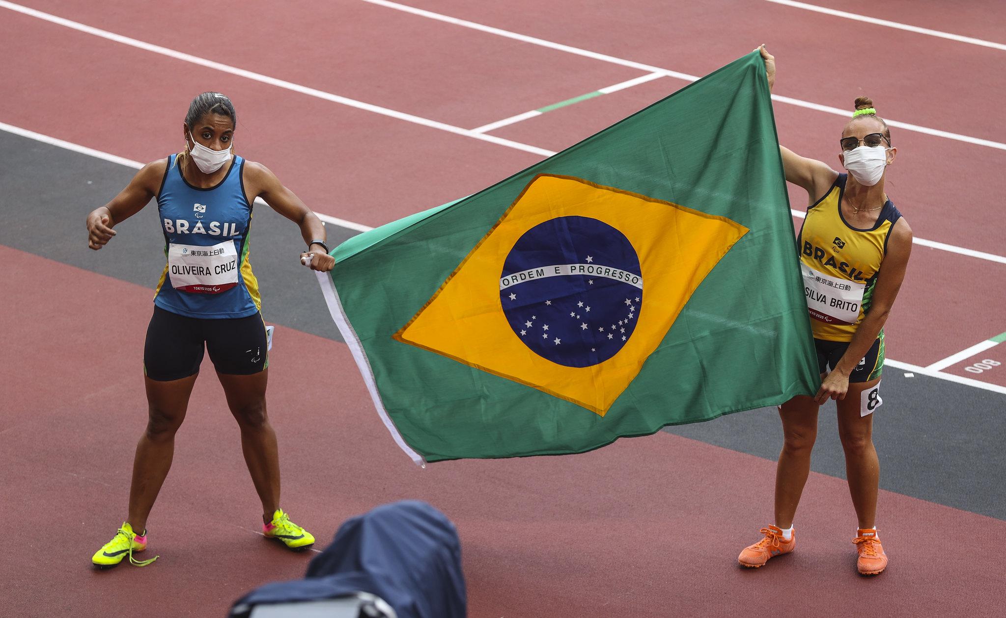 Duas atletas seguram a bandeira do Brasil