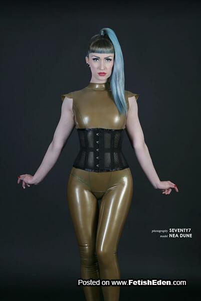 Mustard latex catsuit Nea Dune has aqua hair