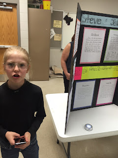 Young girl blonde hair, glasses, wearing all black standing next to her project