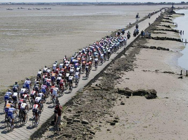 A few cyclists cross the Passage du Grois. The sun is shining and the road (for now) is above water. - Would You Dare Cross This Dangerous Highway In France? Many Try, Few Succeed.