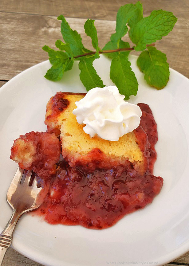 this is a piece of cobbler on a white plate with a sprig of mint on it. The raspberry filling is oozing from under the crust and served warm