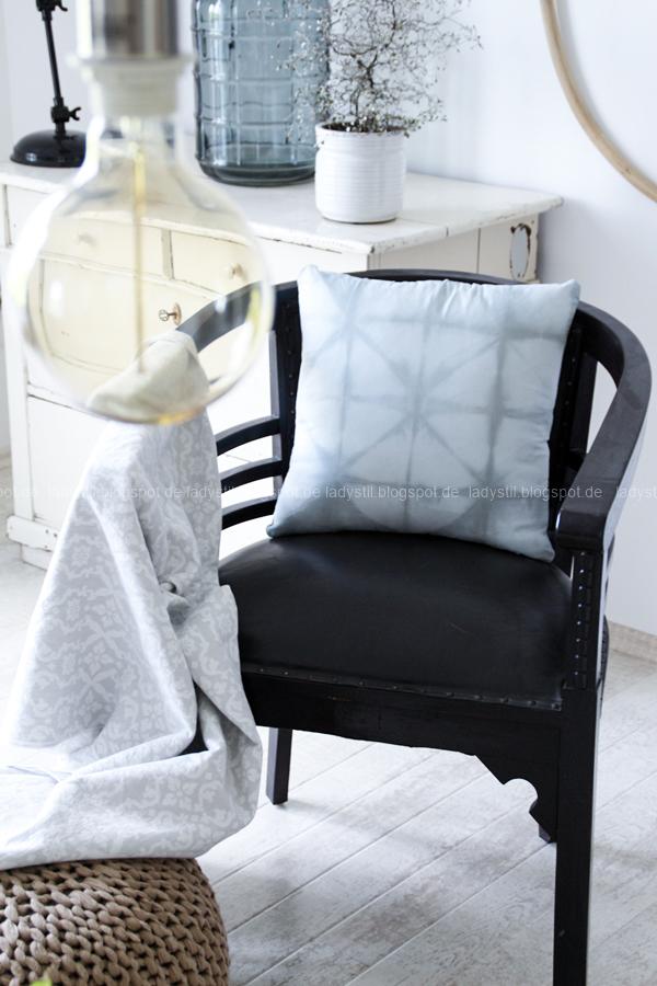 antiker Stuhl mit Shibori-Kissen, im Hintergrund eine beige Kommode mit Zickzackstrauch und grauer Flaschenvase