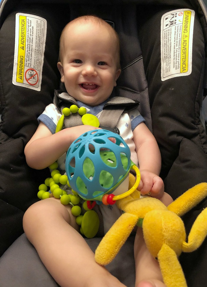 Baby in a car seat with toys for a long road trip