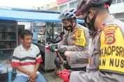 Sambil Patroli Bersepeda, Kapolres Merangin Bagikan Masker Ke Warga