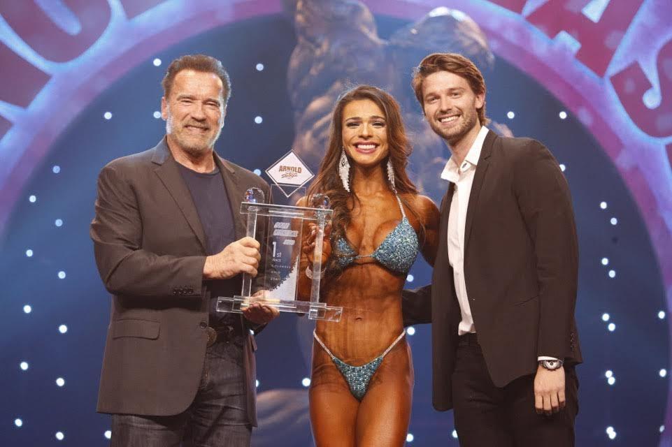 Emocionada, Elisa Pecini recebe troféu de campeã Bikini International 2020 pelas mãos de Arnold e Patrick Schwarzenegger. Foto: Divulgação