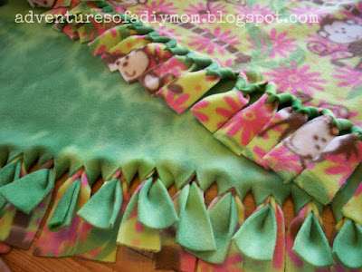 green and pink fleece blanket with fringe.