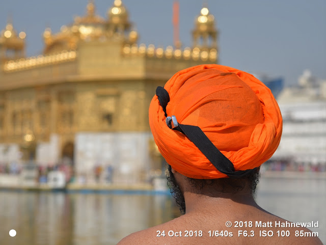 matt hahnewald photography; facing the world; people; head; neck; beard; barechested; orange; dastar; turban; dagger; kirpan; ceremonial; knife; candid; concept; humanity; living; travel; culture; tradition; lifestyle; religion; religious; traditional; cultural; sikh; sikhism; follower; faith; khalsa; temple; holy pond; pond of nectar; sarovar; golden temple; sri harmandar sahib; tourist attraction; devotee; amritsar; punjab; india; asia; asian; indian; punjabi; individual; one person; male; young; man; photo; detail; background; nikon D610; nikkor afs 85mm f1.8g; 85mm; 4 x 3 ratio; resized; 1,200 x 900 pixels; horizontal; street; portrait; closeup; back portrait; golden; outdoor; sunlight; color; iconic; awesome; incredible; authentic