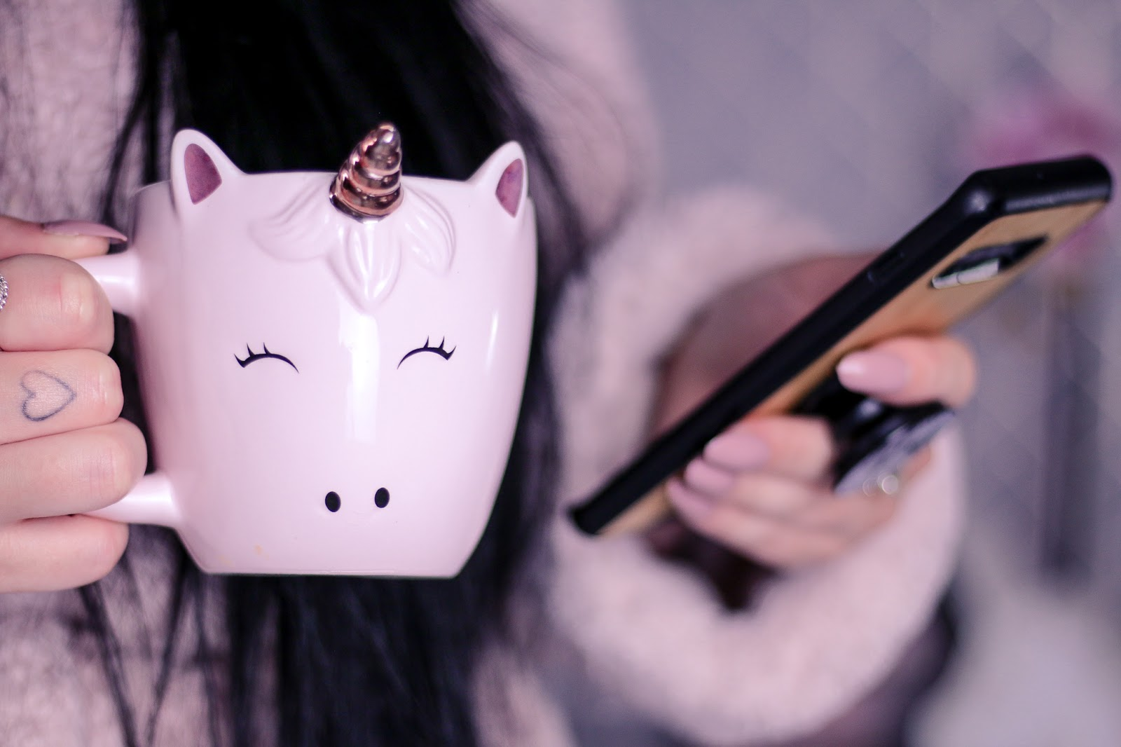 Close up photo of Ofaglasgowgirl in a pink fluffy robe holding a pink unicorn mug and samsung s10+ phone