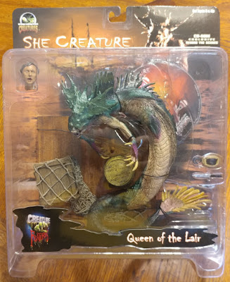 An action figure of the 'She Creature' in its packaging.