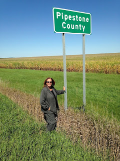 Bev Durgan by Pipestone County road sign