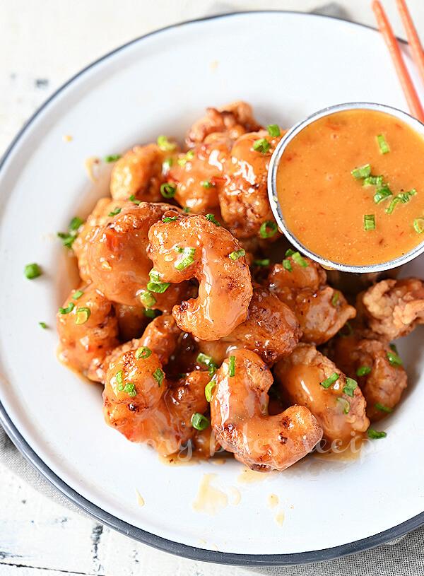 a white plate with cripsy bonefish grill copycat bang bang shrimp served with bang bang sauce