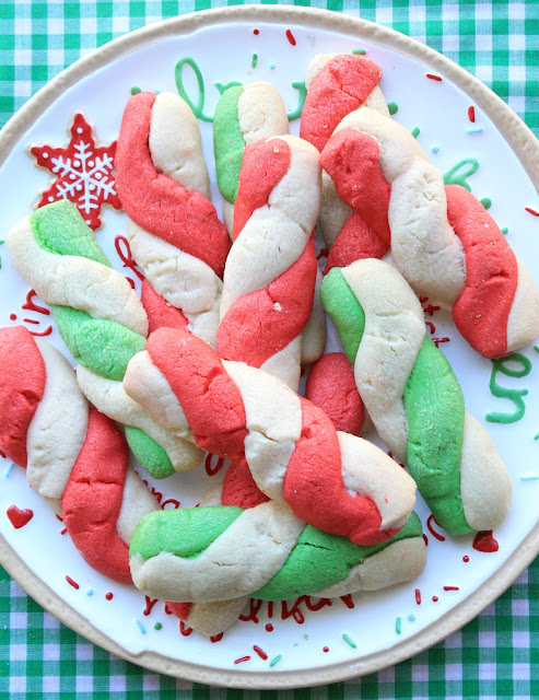 twisted red and green peppermint stick cookies piled on a holiday cookie tray