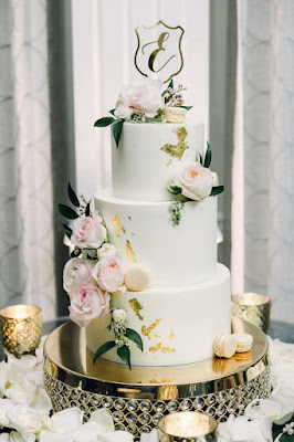 white wedding cake with floral and gold leaf
